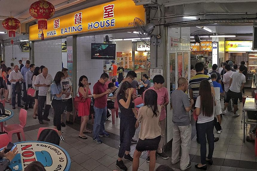 The long L-shaped queue at Hill Street Tai Hwa Pork Noodle during lunchtime yesterday. The hawker stall in Crawford Lane was awarded a Michelin star on Thursday. At 1.10pm yesterday, the queue at the stall grew to about 50 people, and customers said