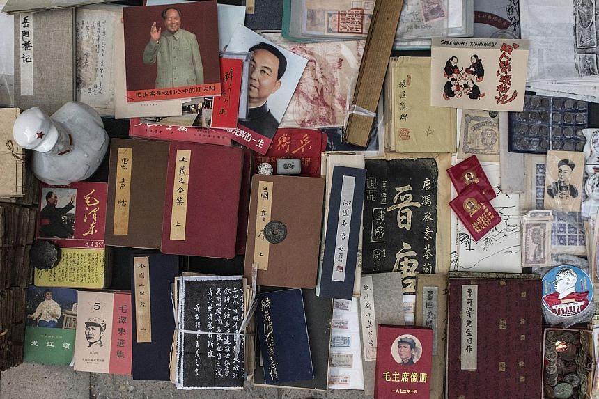 Books, coins and Mao-era objects on display at the Panjiayuan Antique Market in Beijing earlier this month. Collectors of rare books and posters find gems in Panjiayuan's ramshackle alleyways, or make discoveries in its more exclusive little shops.