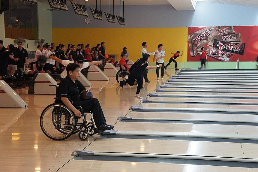National para bowlers Thomas Ong (foreground) and Kalvin Tay (in red) roll off against donors in the inaugural Charity Bowling Challenge hosted by Sponzer, a branding agency founded by Asian Games triple gold medallist Remy Ong. The event, which was