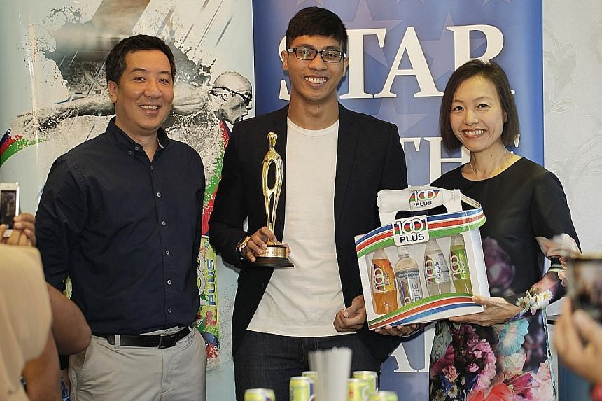 ST sports editor Marc Lim and F&N general manager Jennifer See presenting June's ST Star of the Month award to silat exponent Alfian Juma'en.