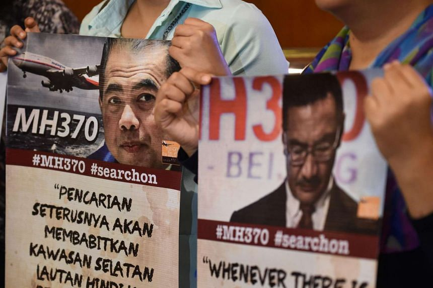 Relatives of passengers missing on Malaysia Airlines MH370 holds placards during a press conference after meeting with the Joint Agency Coordination Centre and Australian Transport Safety Bureau at a hotel in Kuala Lumpur on July 21.