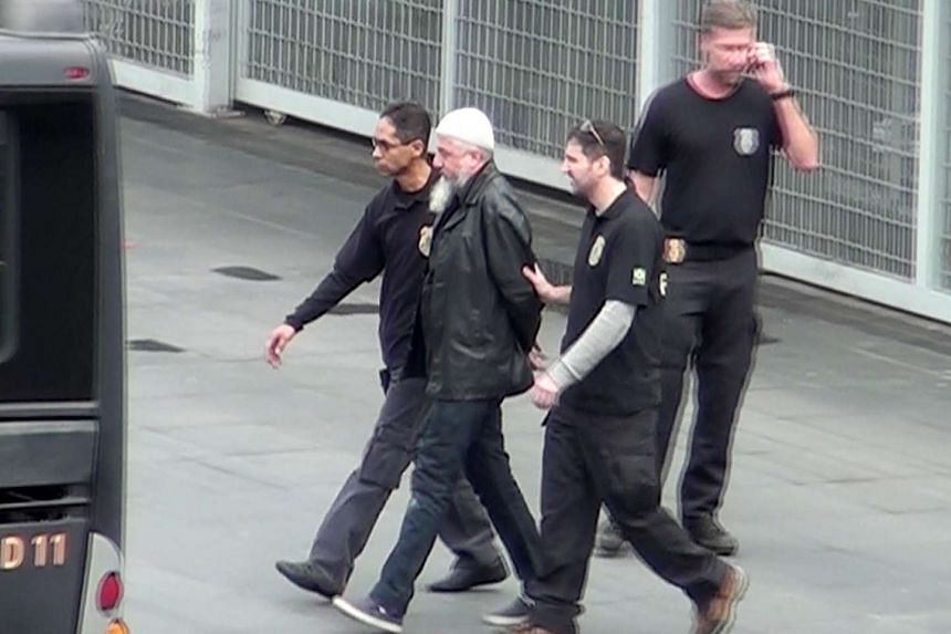Brazilian Federal Police officers escort one of the 10 people they arrested, at the Guarulhos airport in Sao Paulo, in this video frame taken on July 21.