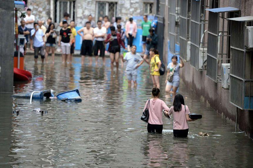 People making their way through a flooded area in Changping District in Beijing on July 21.