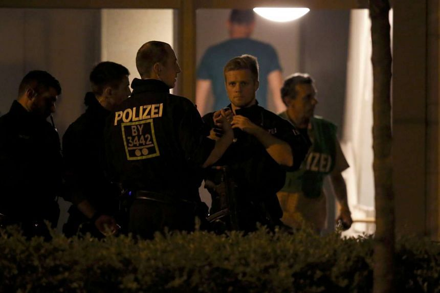 Police officers are on their way to search an appartment building following a shooting rampage at Olympia shopping mall in Munich, Germany on July 23.