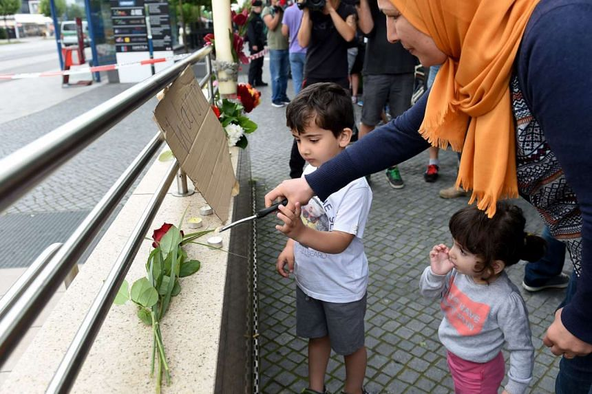 A woman and her children light candles to commemorate the victims at the entrance of the subway station near the shopping mall Olympia Einkaufzentrum in Munich on July 23, 2016.