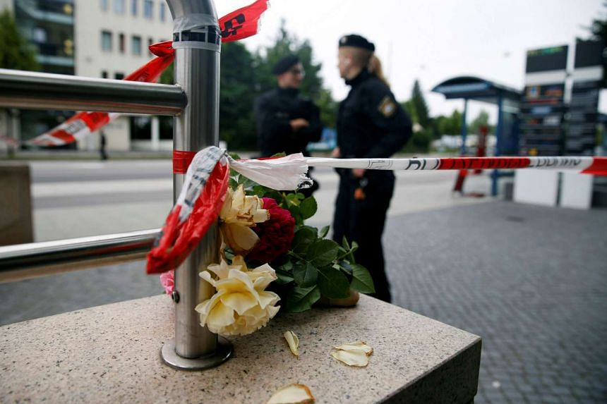 Flowers are placed near the Olympia shopping mall, where a shooting rampage started in Munich, on July 23, 2016.