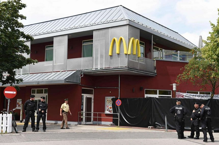 Policemen stand in front of the McDonald's where the Munich shooting occurred on July 23, 2016.