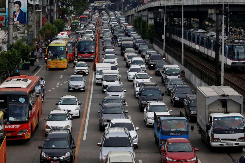 Motorists drive through a heavy traffic flow near a passing metro train along the main highway EDSA in Makati, Manila.