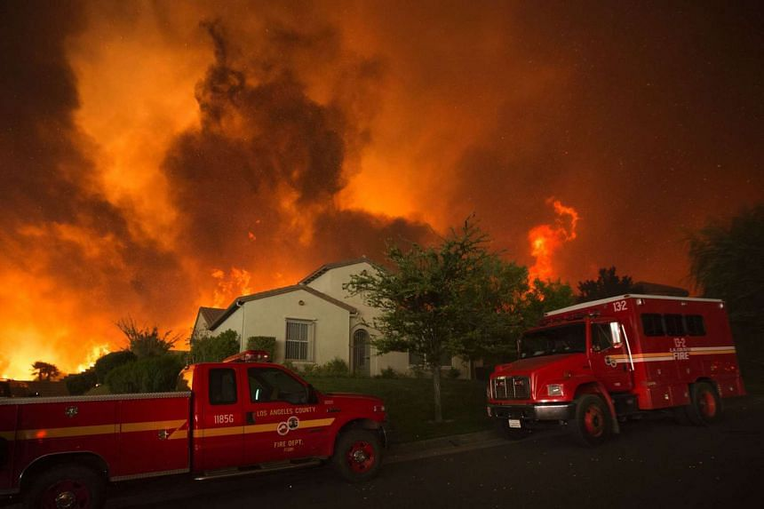 Flames can be seen closing in on homes, near Santa Clarita, California, on July 23, 2016.
