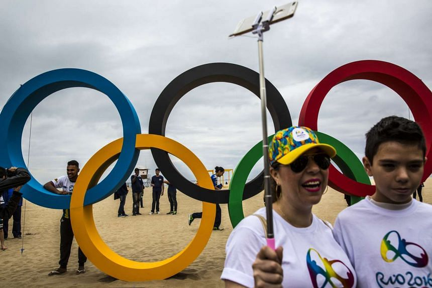 Visitors take a selfie in front of newly unveiled Olympic rings on Copacabana beach in Rio de Janeiro.