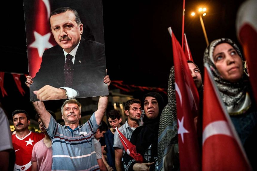 A man holds up a photo of Turkey's President Recep Tayyip Erdogan during a pro-Erdogan rally in Istanbul on July 22, 2016.