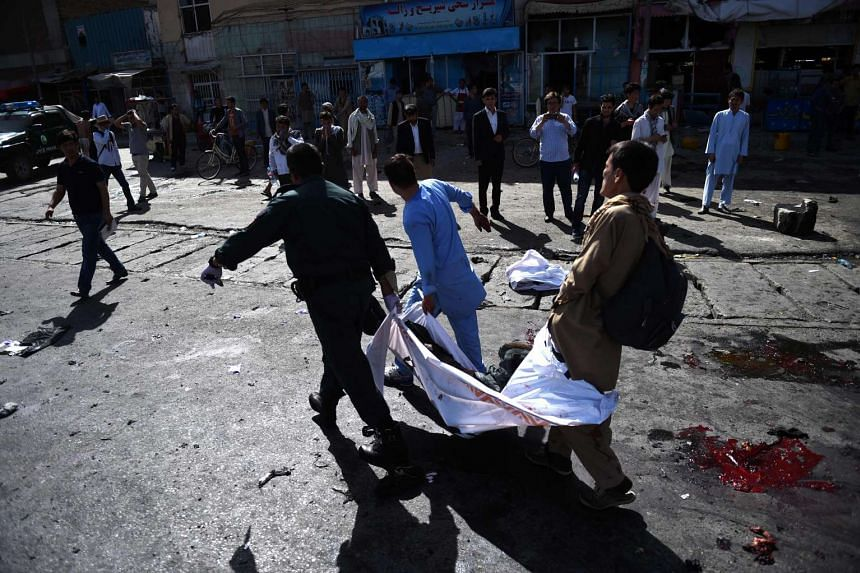 Afghan volunteers carry the bodies of victims fromt the scene.