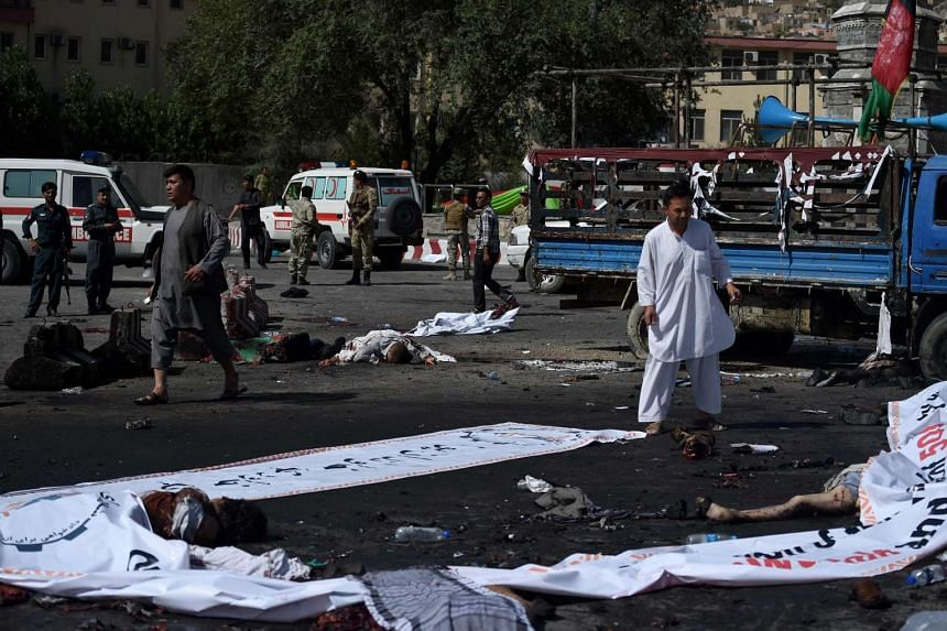 Afghan protesters walk near the bodies of victims at the scene of the suicide attack.