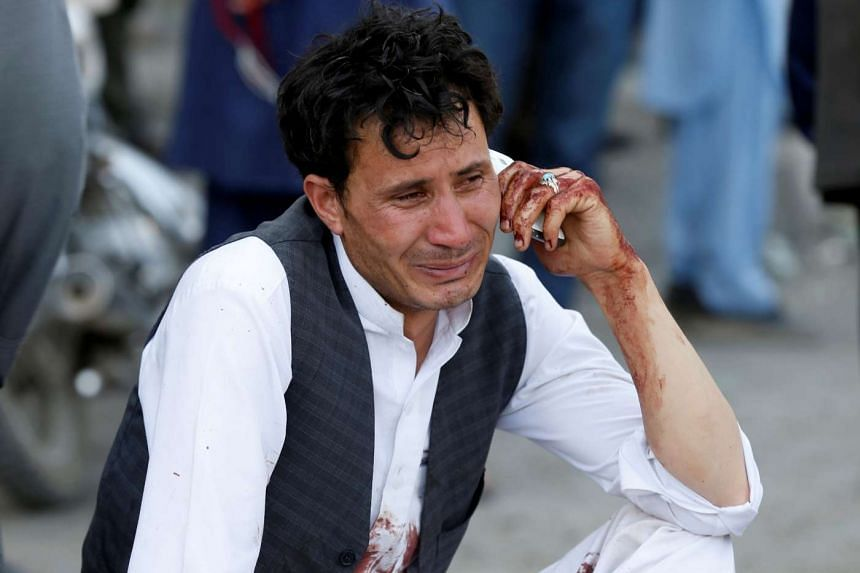 An Afghan man talks on his phone after a suicide attack in Kabul, Afghanistan July 23, 2016.