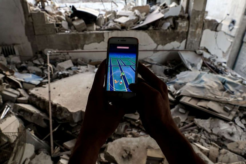 A Syrian gamer plays Pokemon Go amid rubble in the besieged rebel-controlled town of Douma on July 23, 2016.