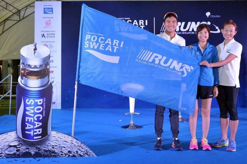 """Pocari Sweat Ambassadors, Mok Ying Ren and Neo Jie Shi, with Ms. Wina Wong, Country Manager of Pocari Sweat  Singapore, planting the Pocari Sweat  flag on the """"Moon""""."""