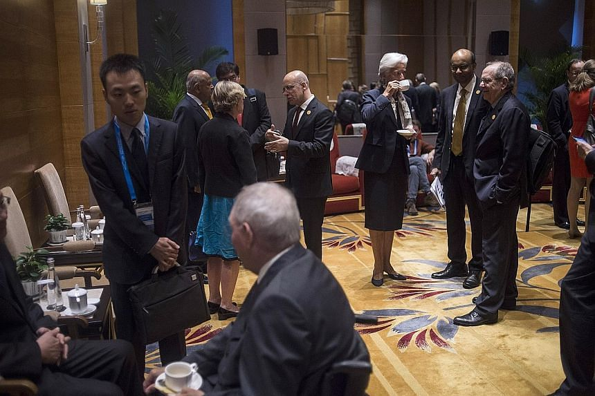 International Monetary Fund managing director Christine Lagarde (third from right) chatting with Singapore's Deputy Prime Minister Tharman Shanmugaratnam (second from right) and Italy's Finance Minister Pier Carlo Padoan (right) before the start of t