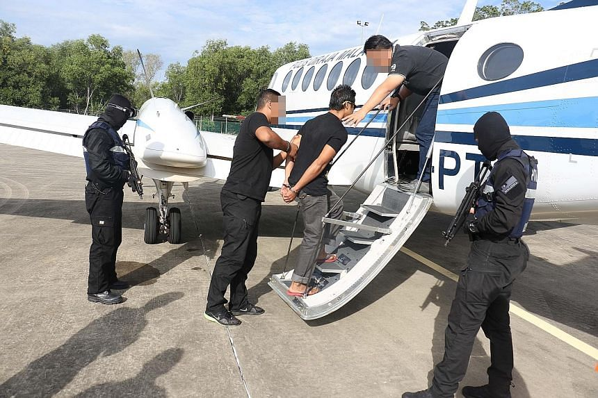 A suspect being escorted onto a plane. The 14 arrested suspects are aged between 20 and 49, and include cooks, a mechanic, a welder and a student. The police did not identify them.