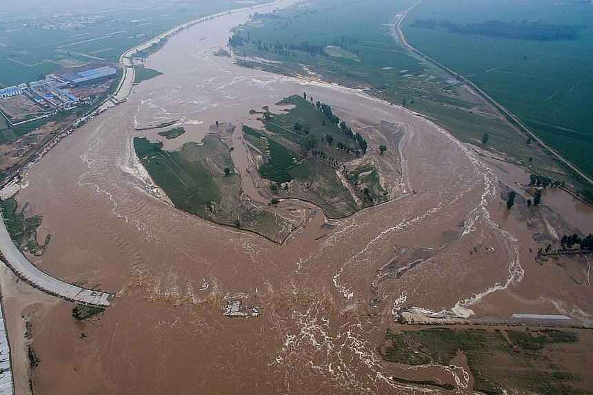 Muddy water gushing over roads and fields in Xingtai. The reason for the flood remains unclear, though some suspect a broken levee.