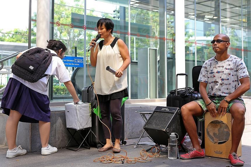One of the grant recipients, Ms Wan, with her busking partner, Mr Ivni, outside Holland Village MRT. The award programme will provide weekly music lessons for Purple Symphony members.