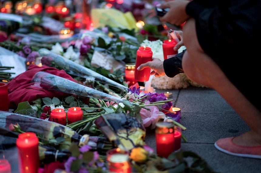 A woman places a candle in front of the Olympia-Einkaufszentrum shopping centre on July 23 in Munich, southern Germany.