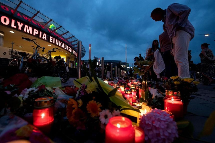 Flowers and candles lie in front Olympia shopping center which was the scene of a shooting spree in Munich, Germany, on July 23.