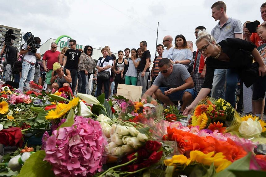 People lay flowers for victims of the Olympia shopping centre attack in Munich.