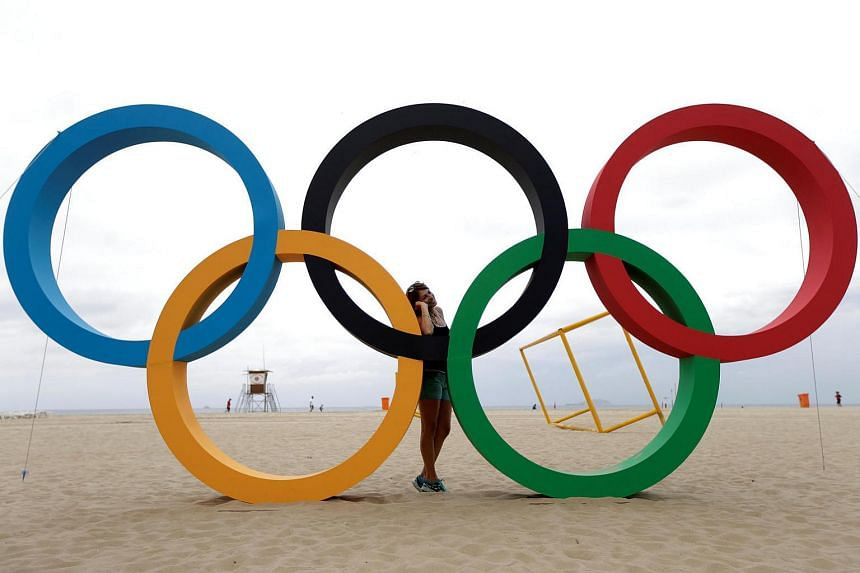 A woman poses with the Olympic Rings ahead 2016 Rio Olympics in Rio de Janeiro, Brazil, on July 21.