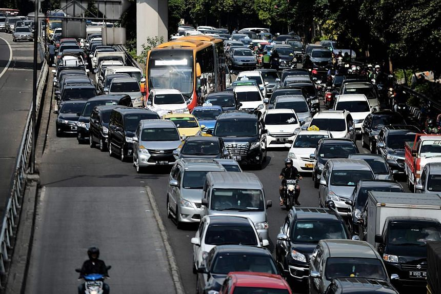 Vehicles commute on a road during afternoon rush hour in Jakarta on June 30.