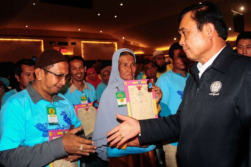 Thai Prime Minister Prayut Chan-o-cha shakes a man's hand at a ceremony to distribute land deeds to locals in Narathiwat, on July 25, 2016.