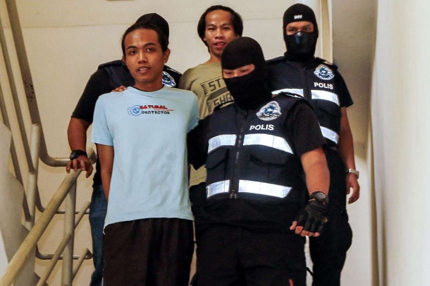 Malaysian anti-terrorism police escort two suspected ISIS militants Imam Wahyudin and Jonius Ondie to the courthouse in Petaling Jaya, on July 25, 2016.
