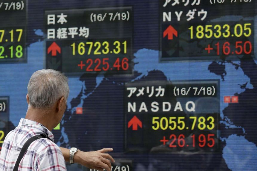 A pedestrian watches a display showing closing information of the Nikkei Stock Average in Tokyo, Japan July 19.