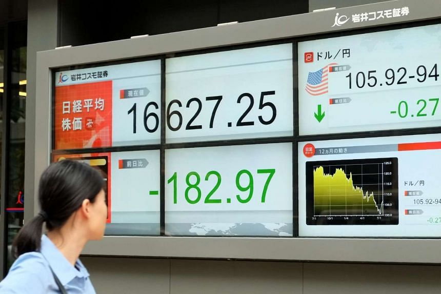 A pedestrian looks at a quotation board displaying share prices on the Tokyo Stock Exchange in front of a securities company in Tokyo on July 22.