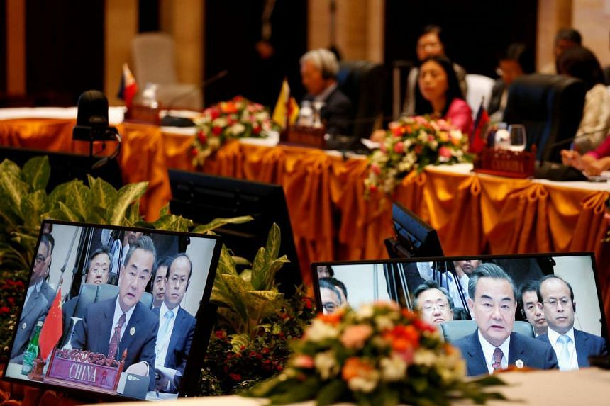 China's Foreign Minister Wang Yi is seen on screens while he speaks during a meeting with Asean foreign ministers in Vientiane, Laos July 25.