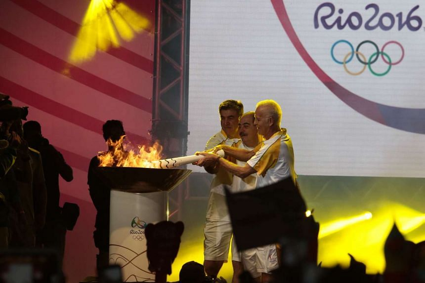 Former football players Ademir da Guia (right), Rivellino (centre) and Zetti light the Olympic torch at Anhembi Park in Sao Paulo, on July 24, 2016.