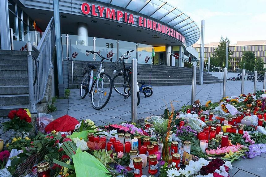A memorial of candles and flowers laid outside the Munich shopping mall.