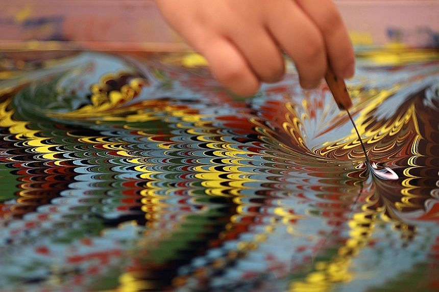 """Turkish visual artist Garip Ay demonstrating one of the oldest forms of painting from Turkey known as Ebru. A pattern emerges after a fine wire comb is """"dragged"""" on a paint-coated surface of water. The pattern is then printed by floating a sheet of p"""