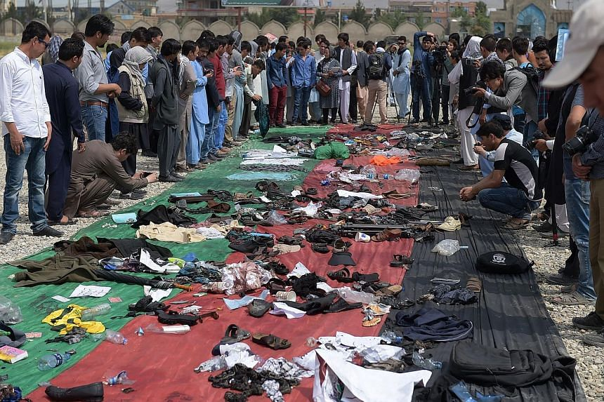 Afghans sorting through the belongings of their relatives and friends killed in the suicide bombing claimed by ISIS.