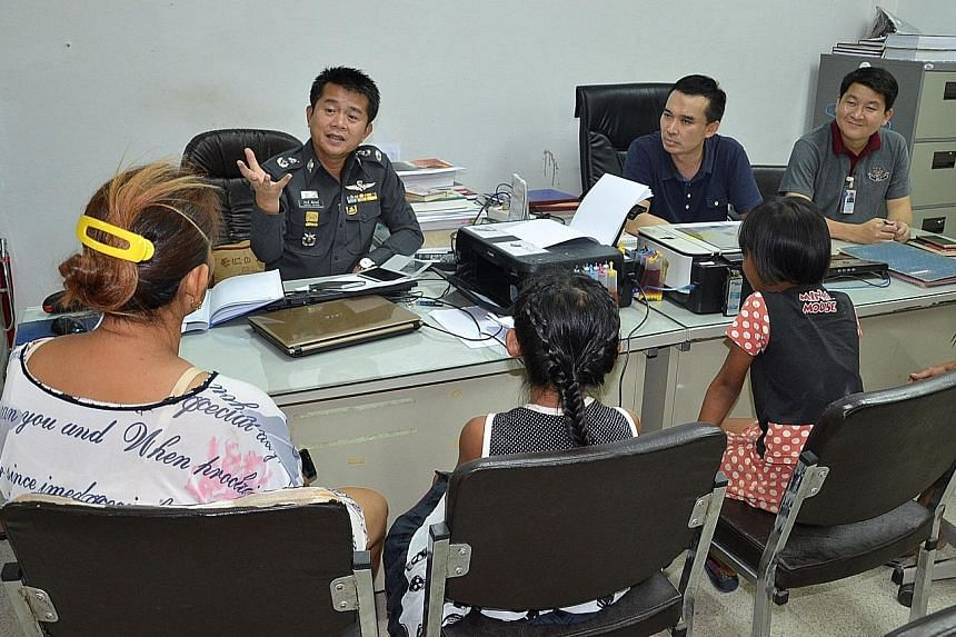 The two girls appearing before Thai police. Officers said rules required charges to be filed even though the girls will not be punished.