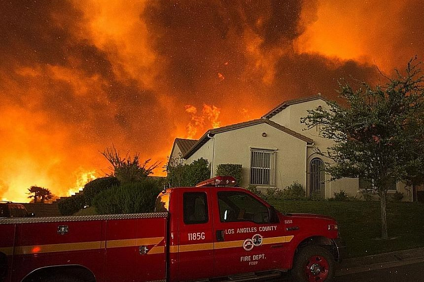 Flames and smoke from the fire looming over a house near Santa Clarita, California, on Saturday. The blaze had blackened some 8,094ha by last Saturday night.