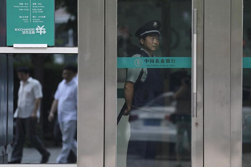 A security guard stands inside a branch of Agricultural Bank of China, in Beijing on June 25, 2015.