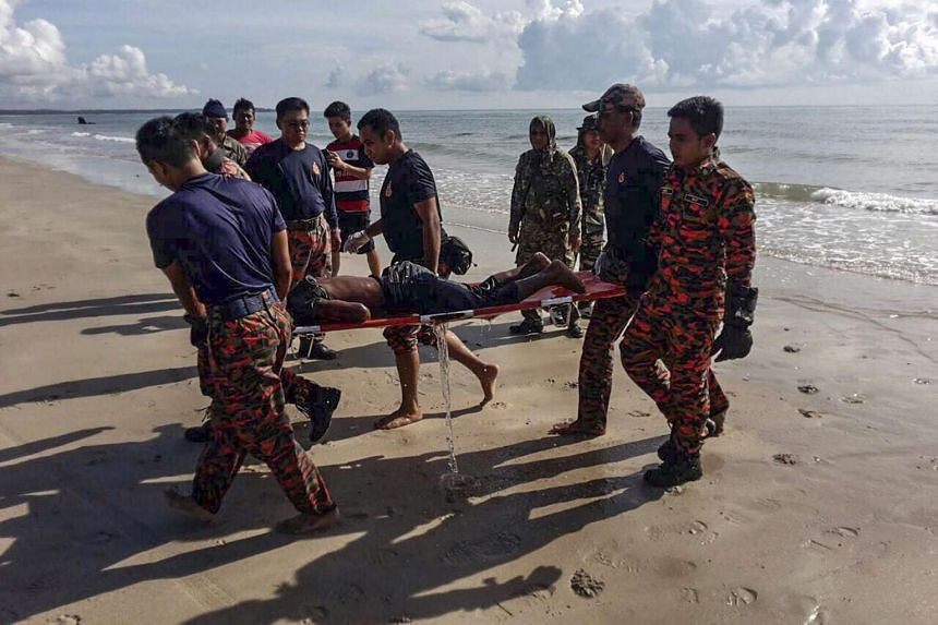 Officers recovering a body after a boat capsized off Batu Pahat on July 24.