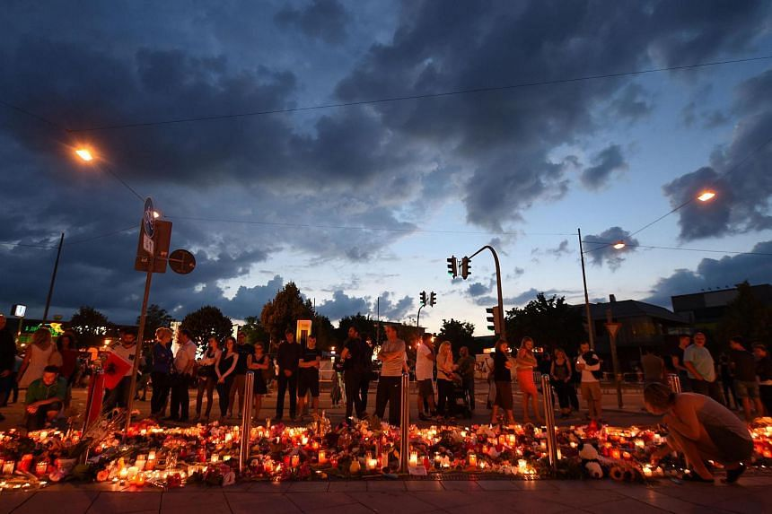 People mourn in front of candles and flowers on July 24 near the Olympia Einkaufszentrum shopping centre in Munich, southern Germany.