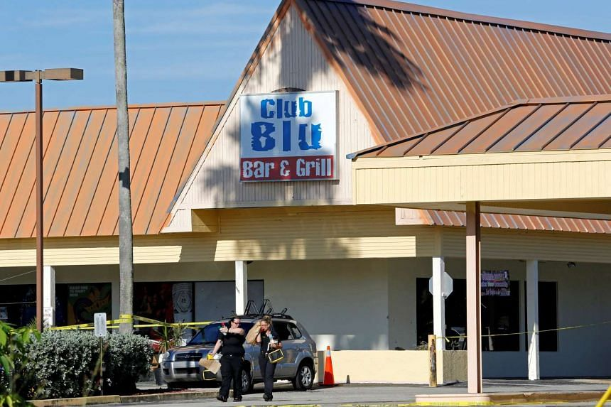 Fort Myers police officers walk in the parking lot of Club Blu after a shooting attack in Fort Myers, Florida, on July 25, 2016.