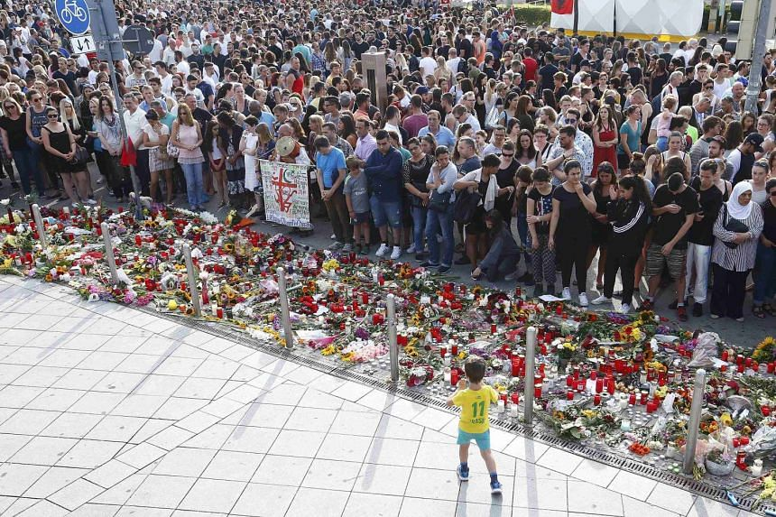 People mourn outside the Olympia shopping mall in Munich, Germany on Sunday (July 24).