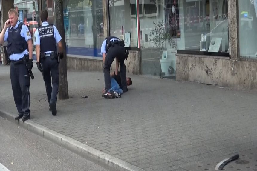 A screen grab taken from video footage shows police arresting Syrian refugee after he killed a woman with a machete and injured two others in Reutlingen, Germany on Sunday.
