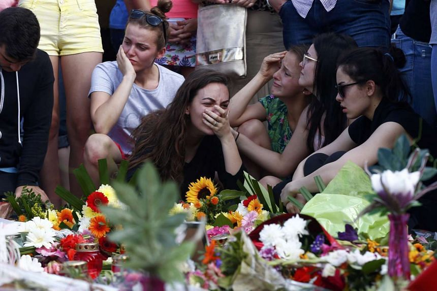 Young women mourning outside the Olympia shopping mall in Munich, Germany on Sunday (July 24).