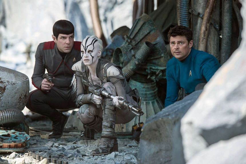 Zachary Quinto (left) as Mr Spock and Karl Ruban as Dr McCoy (right) take cover with Sofia Boutella as Jaylah (centre) in Star Trek Beyond.