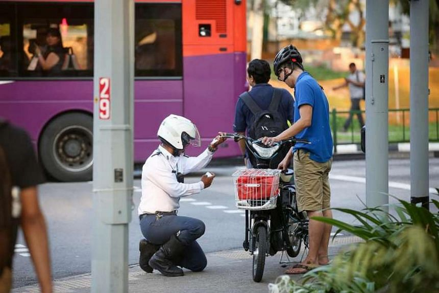 A user of an illegal motorised bicycle being pulled over by an enforcement officer from the Land Transport Authority along Boon Lay Drive on Jan 6, 2016.