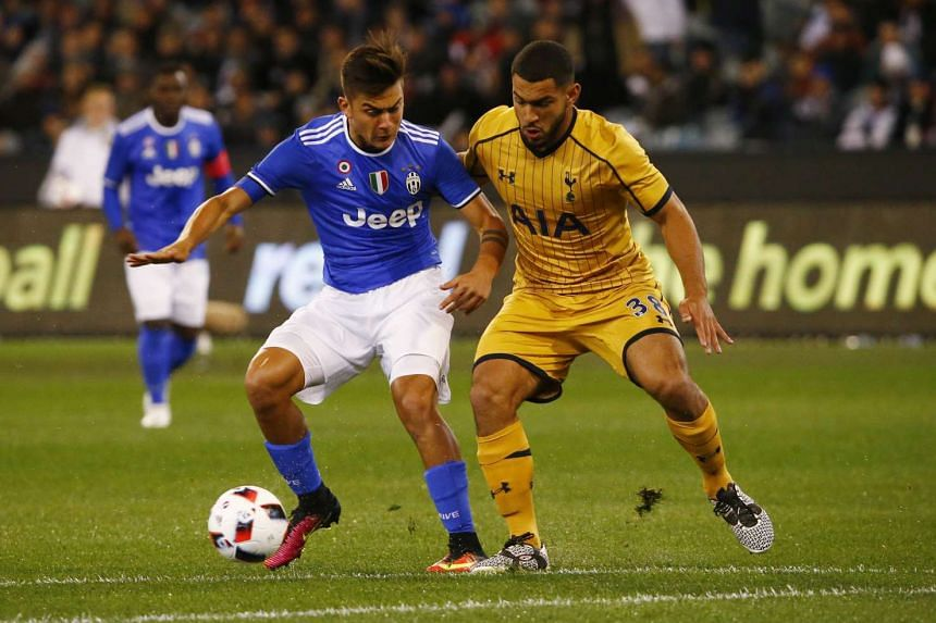 Juventus' Paulo Dybala (left) holds off Tottenham's Cameron Carter-Vickers while dribbling the ball during their match in Melbourne on July 26, 2016.